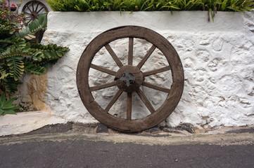 Старое деревянное колесо стоит у побеленной стены.