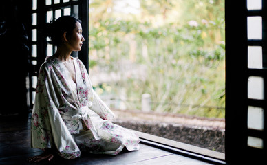 Beautiful Japanese woman in japanese house looking outside to the garden