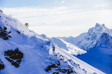 Man skiing steep mountain slope in powder snow with scenic background.