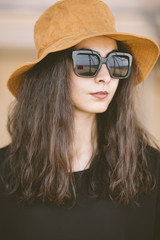 closeup of portrait of real young woman with hat and sunglasses