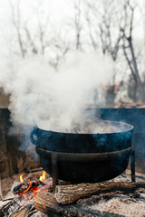 Cooking food on an open fire in a kettle outside