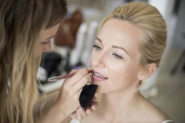 Make-up artist applying lipstick to woman