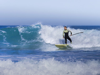 Man surfing with a stand up paddling Board at sopelana beach
