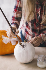 Woman painting white pumpkin with brush