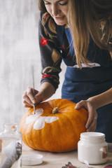 Woman in uniform painting pumpkin with decoupage technique