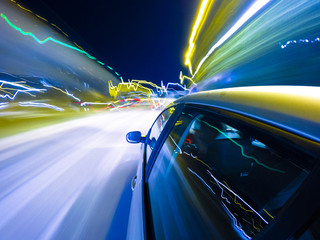 Car driving fast in the night city
