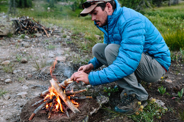 Man gathering wood and assembling small fire for camping