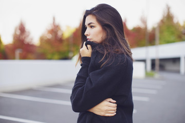 Girl in parking lot looking off into the distance