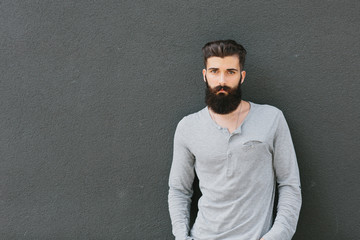 Cool young man standing in front of a gray wall