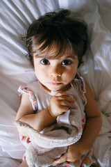 Serious baby girl lying on a bed holding her dou dou, from above