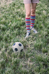 A pair of football kicking legs (with warmers) and feet on a grassy field