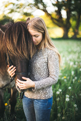 a girl cuddles her horse