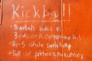 Kickball Rules Written In Chalk On Orange Wall In Playground