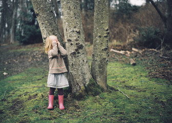 Young Girl plays hide and seek in the woods in early spring