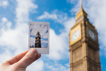 Hand holding an instant photo in front of the Big Ben, London, UK