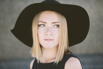 blond woman with black hat