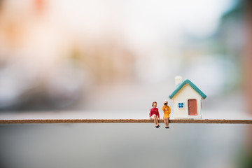 Miniature people, couple woman sitting in front of house