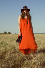 Girl in red dress jumping on the sunny meadow