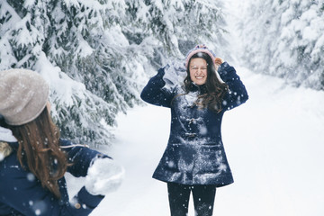 Woman throwing snowball at her girlfriend