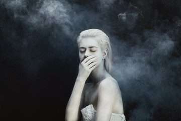 Artistic portrait of a young woman wearing white face paint in a smoke