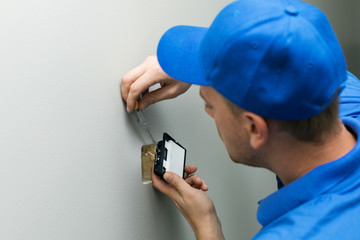 electrician installing light switch on the wall