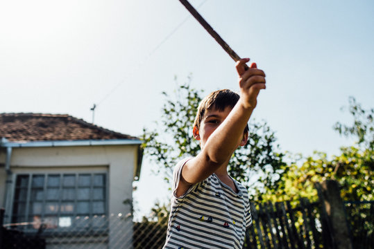 Close up shot of boy running with a wooden stick