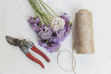 Roll of string next to flowers and garden cutters on white