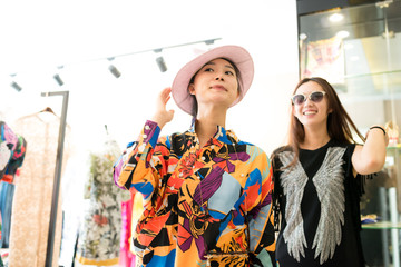 Two young fashion girl shopping at clothing store