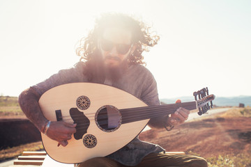 Portrait of Bearded Young Hippie Wearing Sunglasses and Playing Oud (Mandolin)