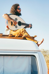 Cool Bearded Young Man Sitting on Roof of White Camper Van and Playing Oud (Mandolin)