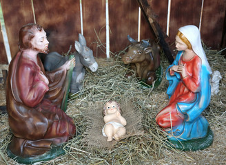 nativity scene with statues of the Holy family praying in the ma