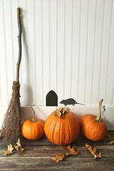 Pumpkins and broom leaning against wall