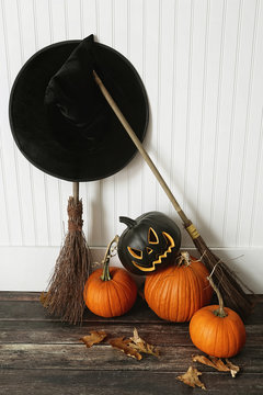 Witch hat, broom and pumpkins near wall on floor