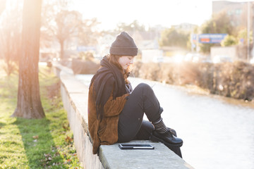 young woman sitting outdoor using tablet listening music
