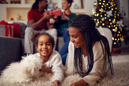 smiling sisters are playing with dog They are lying on floor near Christmas tree.