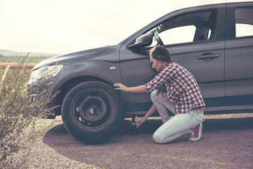 .Beautiful young woman changing tires on her car
