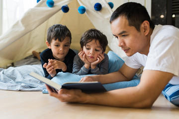 father reading to his young sons