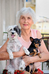 happy senior woman hugging her two dogs