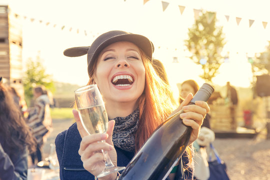 Happy young woman drinking wine having fun outdoors