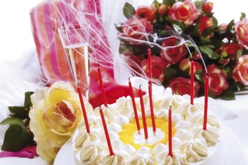 Blown-out candles on a birthday cake, bouquet of roses and a gift in the background