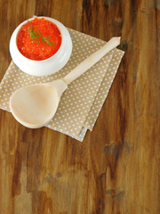 Red caviar in a white ceramic bowl and a wooden spoon on a wooden table