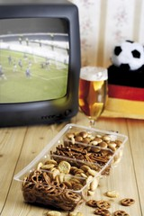 Retro football broadcast - TV broadcast of a game, football hat, glass of beer and a tray of crackers