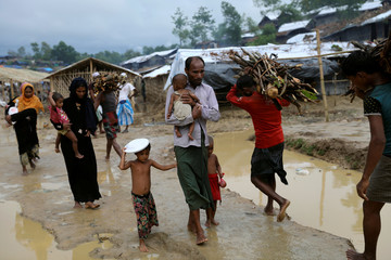 Rohingya refugees walk along the Balukhali refugee camp after the rain in Cox's Bazar