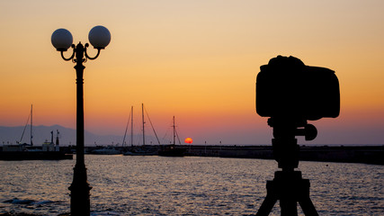 Camera on tripod with sea and sunset in background / Gouves, Crete, Greece