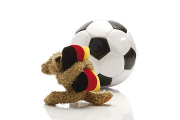 Teddy bear holding a cushion in the colours of the German flag standing in front of a football