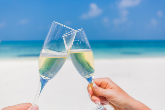 Hands holding champagne glasses on the beach, romantic concept