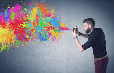 Hipster guy with camera and paint splash