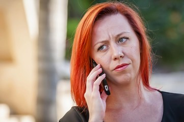 Portrait of a skeptical beautiful Caucasian red hair woman talking on a phone with somebody. Young girl argues with boyfriend