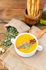 bowl of delicious pumpkin soup. Rustic background