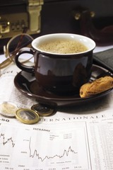 Cup of coffee and Euro coins on stocks page
